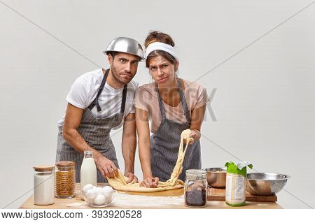 Horizontal Shot Of Tired Housewife And Husband Prepare Dough With Flour For Baking Bread, Try New Re
