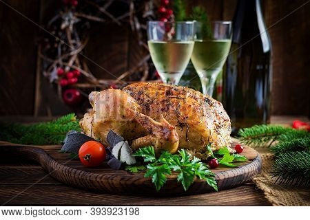 Baked Turkey Or Chicken. The Christmas Table Is Served With A Turkey, Decorated With Bright Tinsel.