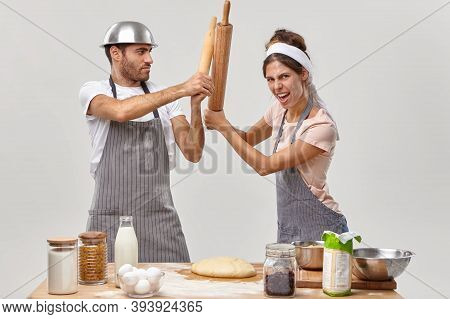 Two Opponents At Kitchen. Woman And Man Cooks Struggle With Kitchen Utensils, Compete Who Cooks Bett