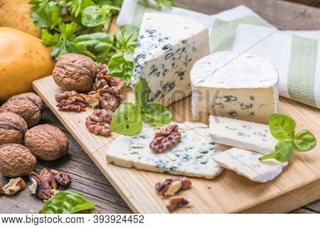 Fourme D'ambert Blue Cheese  And Walnuts. Wooden Background. Top View Segment Of Blue Cheese Or Camb