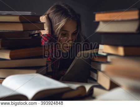 Concentrated Young Woman Student Studying In Library. Female Student Read.  Focused Girl Studying An