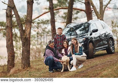Happy Family Sitting And Having Fun With Their Dog Near Modern Car Outdoors In Forest.