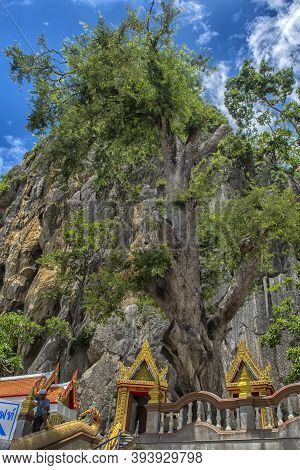 Thailand, Phetchaburi 19.07.2019 View Of Wat Tham Khao Yoi Cave, Buddhist Temple With Green Tree And