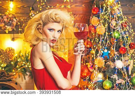 Beautiful Blonde Girl Over Christmas Tree. Retro Pin-up Woman Posing On Vintage Wooden Christmas Bac