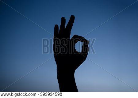 Sign Ok Silhouette. Man Hand Shows Sign Okay. Silhouette. Sign Okay. Ok.