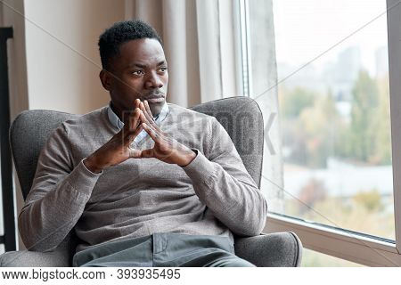 Confident Serious Focused Stylish Rich African Black Man Sitting In Chair At Home Looking Away Throu
