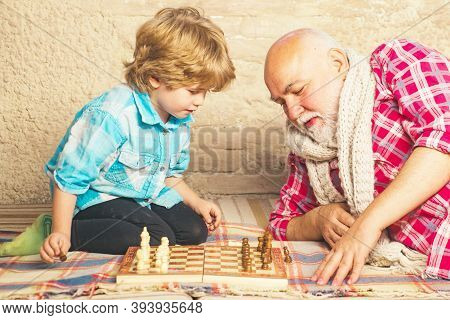 Mature Man With Little Boy Playing Chess. Checkmate. Cute Little Boy Playing Chess. Childhood. Grand