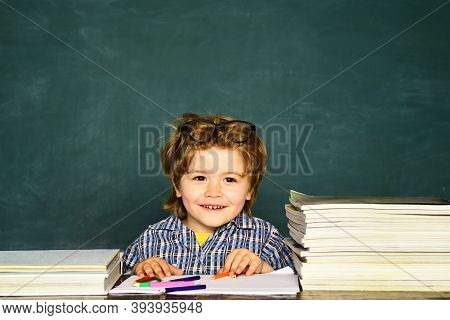 Funny Little Boy Pointing Up On Blackboard. Little Student Boy Happy With An Excellent Mark. Classro