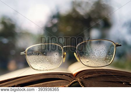 Glasses And Open Book On The Window Sill, Selective Focus