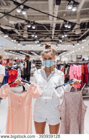 Young Woman Shopping Apparels In Clothing Boutique With Protective Face Mask