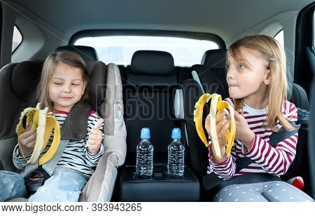 Little Girls, Sisters Are Driving In Car, Eating Banana. Traveling On Road In Safe Baby Seats With C