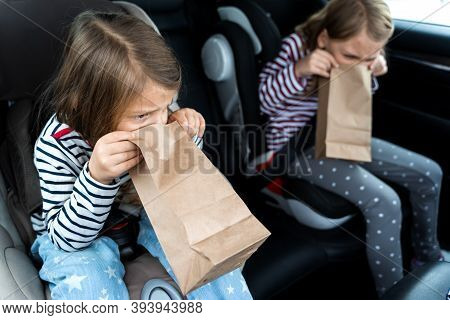 Little Girls, Sisters Are Driving In Car. Children Are Sick, Vomit Into Paper Bag. Traveling On Road