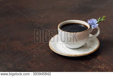 Chicory Drink In A Cup And A Blue Chicory Flower On A Dark Brown Background. Coffee Substitute. Spac