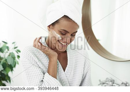 A Smiling Woman In A Bathrobe And A Towel On Her Head Applies Moisturizer From A Jar To Her Face In