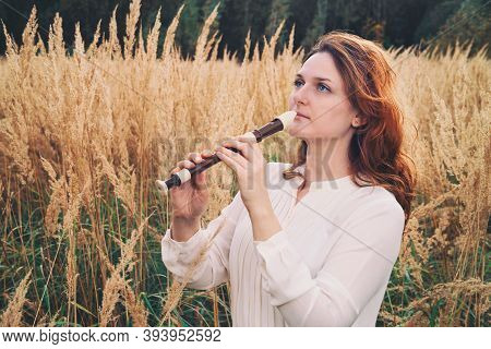 A Flute Player Holds A Black Flute While Standing In The Autumn Field, Beauty