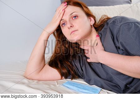 A Young Red-haired Woman Has A Sore Throat Due To A Coronavirus. Redhead Woman Lies In Bed At Home A