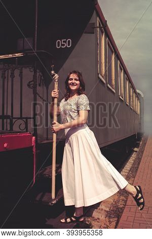 A Woman Stands On The Steps Of The Cars Train. Vintage Train Is At The Station ?? Smoke, Embarkation