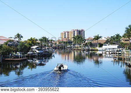 Boat Navigating Beautiful Canal In Sunny Florida