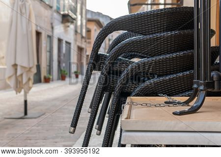 Tables And Chairs From The Terrace Of A Cafeteria, Picked Up And Tied By A Chain. Image Of A Restaur