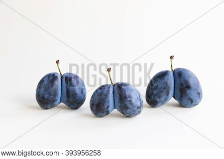 Ugly Organic Blue Double Plums Heart-shaped On A White Background. The Ugly Produce Trend Is The Sal