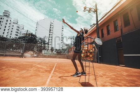 A Young Slim Sport African-american Woman Is Having A Warm-up Session On A Tennis Court, She's Hitti