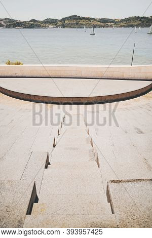 Vertical Shot Of Rows Of Stone Or Marble Seats And A Flight Of Stair In The Center Of A Modern Outdo