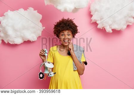 Coming Maternity. Positive Pregnant Woman In Third Trimester Poses With Mobile And Bodysuit For Baby