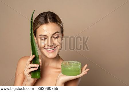 Smiling Happy Young Female Model Holding Aloe Leaf And Jar Of Aloe Gel On Beige Background. The Conc