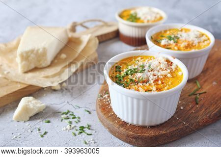 Dietetic Food.  French Cuisine.  Three Servings Of Carrot Flan With Grated Parmesan Cheese. Focus Se