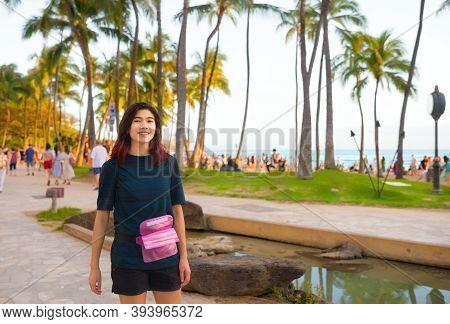Smiling Teen Female Toursit Standing Along Kalakaua Road Near Kuhio Beach In Waikiki, Honolulu,  Haw