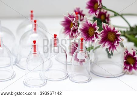 Jars For Hijama On A White Wooden Background And Pink Harezantems. Bloodletting. Sunnah Treatment. I