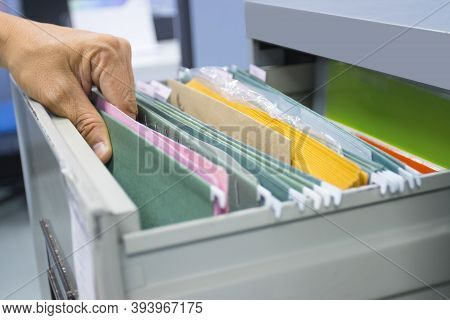 Hand Of Man Search Files Document In A File Cabinet In Work Office, Concept Business Office Life.