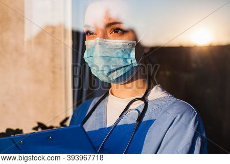 Young Sad Female Caucasian Uk Us Nhs Ems Doctor Carer Looking Through Icu Window,fear Uncertainty In