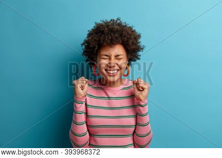 Joyous Female Winner Stands With Clenched Fists And Closed Eyes, Anticipates Excellent News, Rejoice