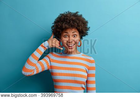 Give Me Call Sometimes. Cheerful Satisfied Afro American Woman Makes Call Me Gesture, Keeps Connecti
