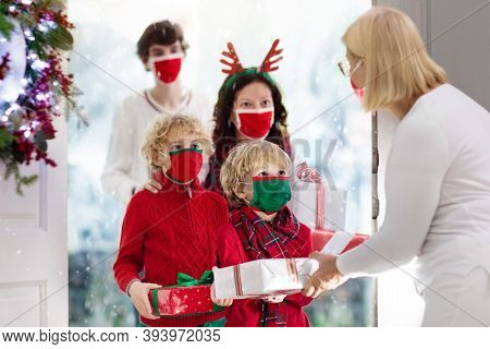 Family With Child At Grandmother On Christmas Day In Covid-19 Outbreak. Kids In Face Mask With Gifts