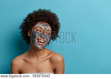Joyful Positive Dark Skinned Curly Woman Stands Naked Indoor, Applies Beauty Mud Mask For Perfect So