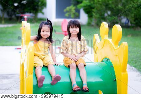 The Two Little Girls Smiled A Little, Sitting On A Tube Of Yellow-green Players. An Asian Girl Is We