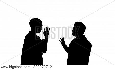 The Silhouette Of A Man And Woman Talking In A Serious Conversation.
