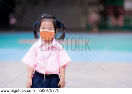 Children Wearing Brown Cloth Face Masks To Protect Virus. Asian Girl Stands In School Grounds. Stude