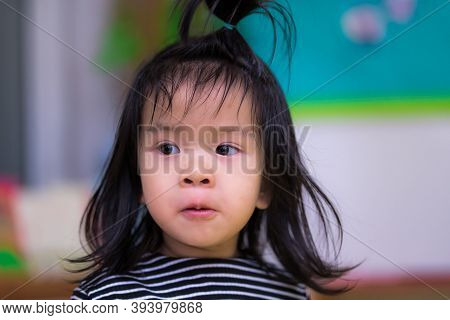 Asian Making Face Curious, Child Black-haired. Kid Wore A Black And White Striped Shirt. Cute Child