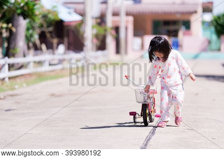 Adorable Asian Child Girl Is Wearing Pajamas Walking On The Street. Children Is Dragging The Tricycl