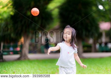 Happy Asian Girl Aged 3 Years Old Throws Tiny Orange Ball Playing Alone On Green Lawn At Park In Aft