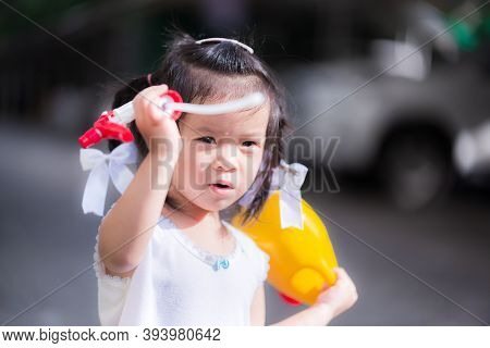 Adorable Little Girl Playing Watering Can With Spray Nozzle. Child Disassembles Head Of Watering Can