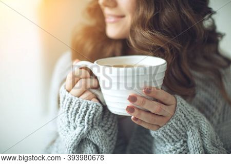 Close-up Of Female Hands With A Mug Of Drink. Beautiful Girl In A Gray Sweater Is Holding A Cup Of T