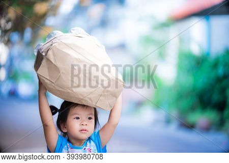Cute Asian Little Girl Collects Plastic Bottles In Paper Bags For Waste Separation And Reuse. 3 Year