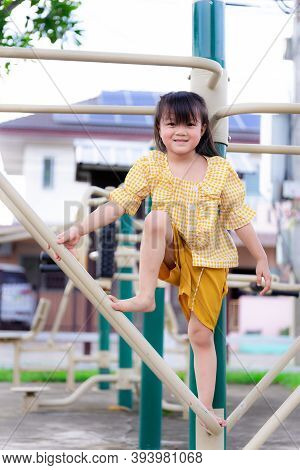 Active Little Girl Climbs Exercise Machine In Mischievous Way At Playground Park. Child Was Wearing