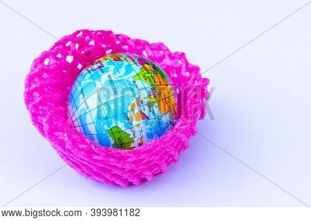 Concept Of Global Warming. The Globe Is Wrapped In Red Plastic Bubbles. Plastic For Fruit Wrapping F