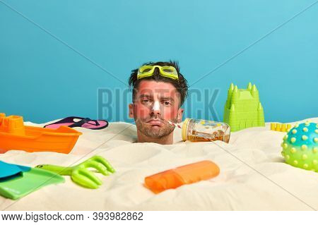 Summer Vacation Concept. Displeased European Man Buried In Sand, Poses On Seashore During Beautiful