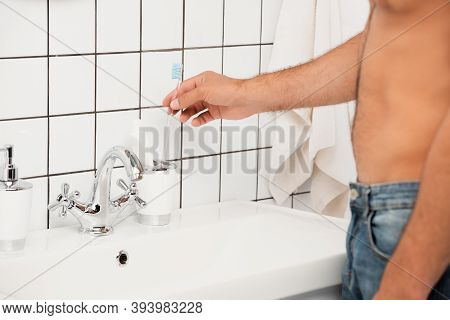 Cropped View Of Man Taking Toothbrush From Toiletries Near Sink In Bathroom